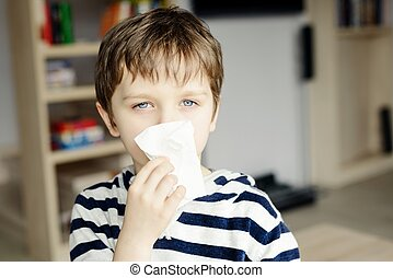Little boy blows his nose