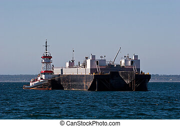 Tugboat Tied to Barge - A red and black tugboat tied to a...