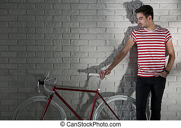 My bike is my friend - Young man and red bike, brick wall in...