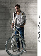 We're ideal couple! - Sporty man and his bike, brick wall in...
