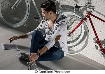 Checking how to improve my bike... - Young man sitting on...