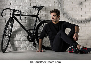 This bike suits me... - Man sitting on floor next to a black...