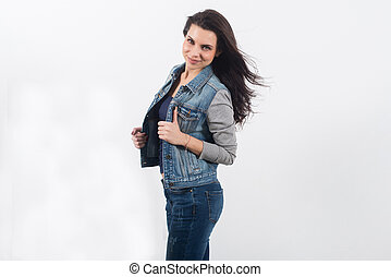 Beautiful young woman posing in jeans on white wall