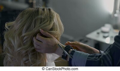 in a beauty salon eccentric stylist makes professional styling for the girls. hairstyle for blonde