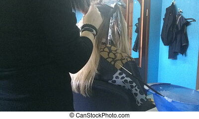 Hairdresser does highlighting to the girl using tools and a...