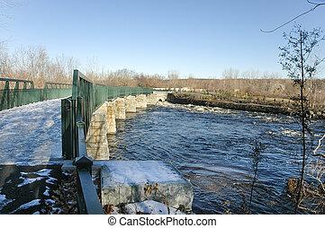 Bridge over fast moving waters - Icy footbridge crosses...
