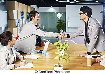 asian business people shaking hands - young asian business...
