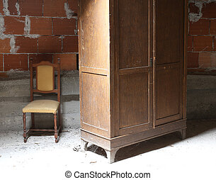 old wooden wardrobe in the dusty attic and a chair
