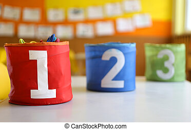 jars with large lettering one two and three on the table in the kindergarten
