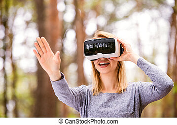 Woman wearing virtual reality goggles outside in spring...