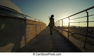 Silhouette of dancing girl - In sun backlit Olympic Park and...