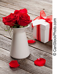 Red rose flowers in pitcher and gift box