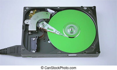 Isolated hard drive from the computer with a green disc -...