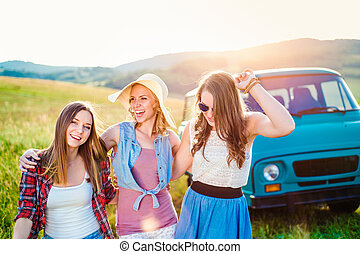 Three teenage hipster girls on a roadtrip, summer day -...
