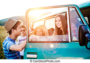 Group of teenage hipsters on a roadtrip, campervan - Group...