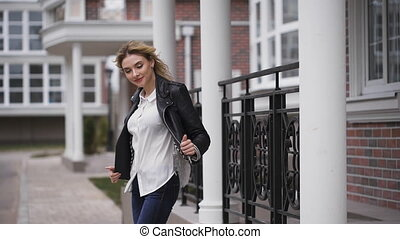 The blonde in a black leather jacket, smiling, to her a little bit cool. Around the house is made of brick.