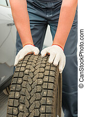 car tire and mechanic hand gloves closeup