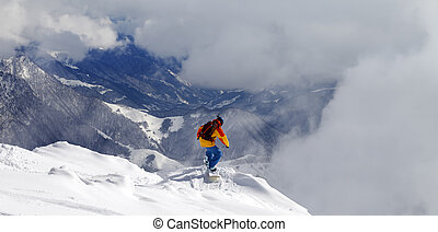 Snowboarder on off-piste slope an mountains in fog Caucasus...