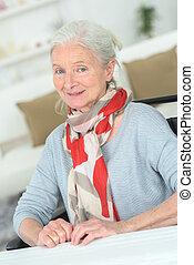 Senior woman sat at a table