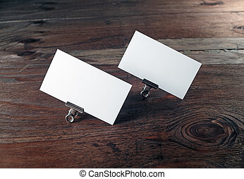 Blank business cards in paper clips on dark wooden...