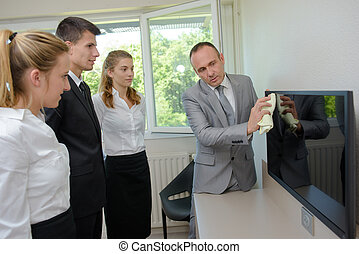 Trainee cleaners watching supervisor clean television screen