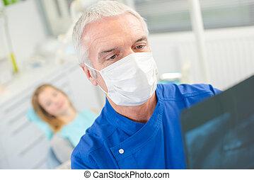 Dentist looking at an x-ray