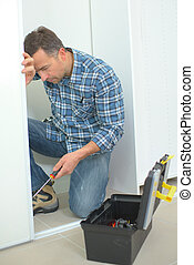 Man holding screwdriver working on doorframe