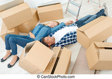 Exhausted couple laying amongst cardboard boxes
