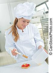 Chef glazing strawberry tart