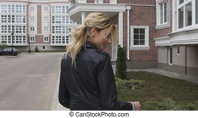 Young woman walking on the street. Blonde turns flirting...