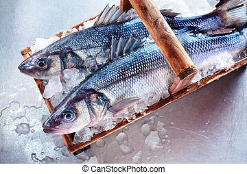 Two whole fresh Loup de Mer or Mediterranean sea bass on a...