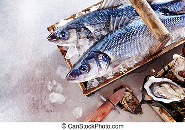 Two fresh Mediterranean sea bass or Loup de Mer on ice in a...