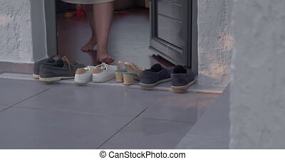 Woman putting on shoes by the house - Woman walking out the...