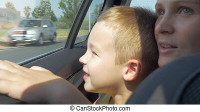 Mother and son looking out car window