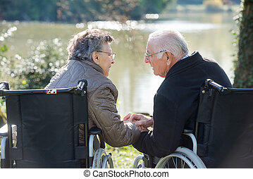 Couple in wheelchairs holding hands