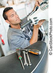 Mechanic repairing scooter