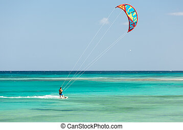 kitesurfer surfing on a flat azure water of Atlantic ocean...