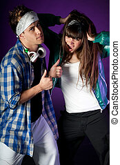 Young urban couple dancers on dark purple light background