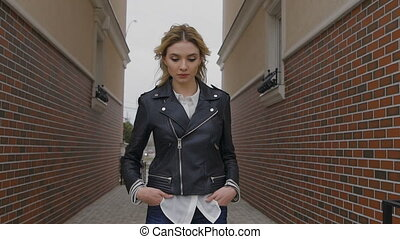 beautiful young woman walking on the street. Blonde...
