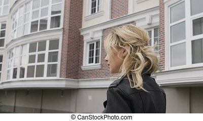 Young woman walking on the street. Self-confident blonde striding purposefully down the street. Black leather jacket