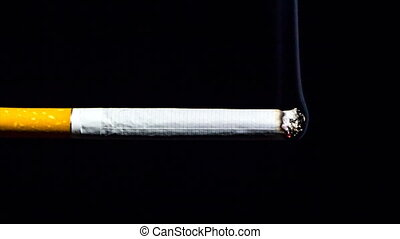 Time lapse of smoldering cigarette on black background