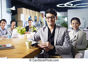 young asian entrepreneurs meeting in office - a team of...