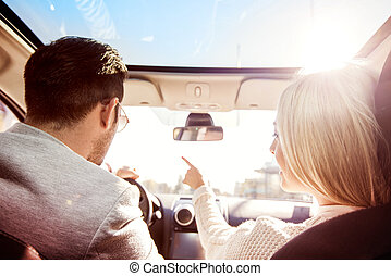 On the road - A young woman and a young man are laughing in...