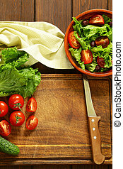 cooking vegetable salad tomatoes, lettuce, cucumbers on a...