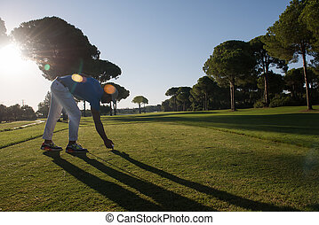 golf player placing ball on tee beautiful sunrise on golf...