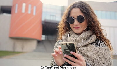 Amazing young woman wearing sunglasses chatting with her friends in the street.