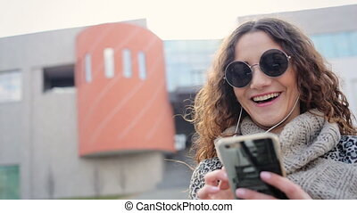 Adorable young smiling lady in headphones chatting with her friends in the street.