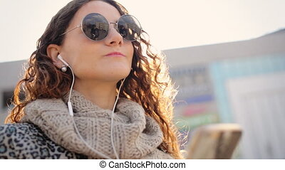 Attractive young lady listening music on her phone in the street.