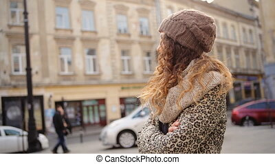 Amazing young woman wearing stylish brown hat standing in the street.