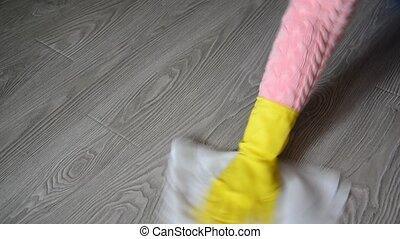 female hand in rubber glove cleaning floor - female hand in...